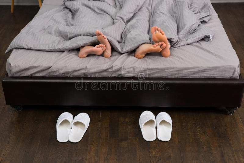 Male and female feet under grey blanket, near two pairs of white royalty free stock photography