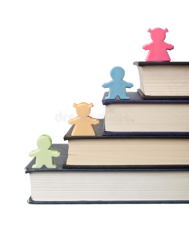 Male and female figurines on stack of books stock photography