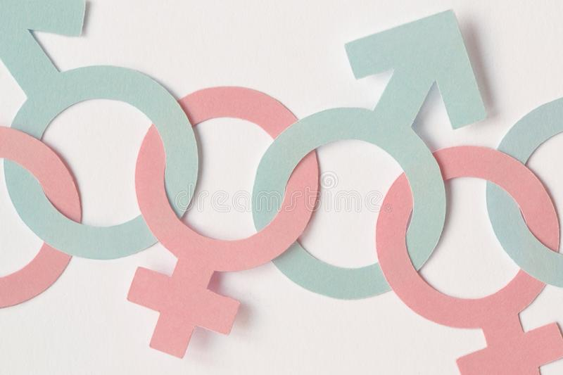 Male and female gender symbols chained together - Gender relations concept stock photos