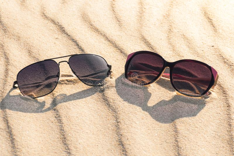 Male and female glasses on sandy beach. stock photos