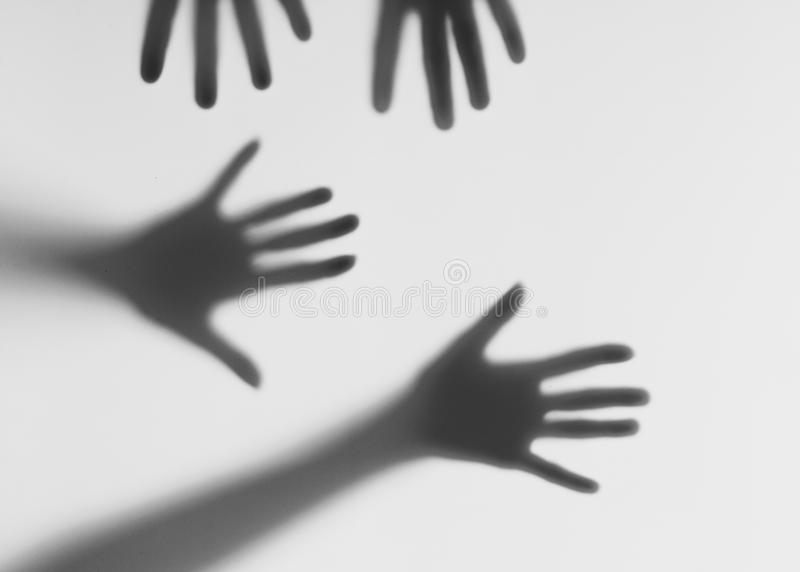 Silhouettes of male and female hands. Conceptual scene. Male and female hands behind a frosted glass stock photo