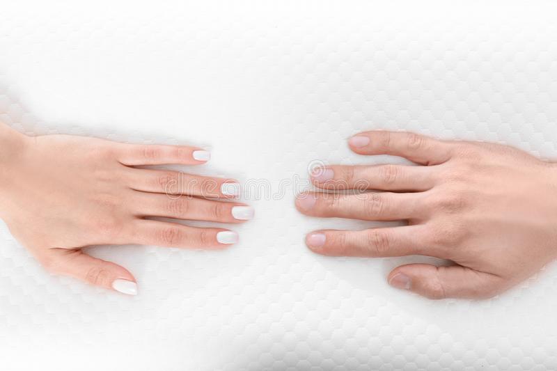 Male and female hands on orthopedic pillow. Healthy posture concept royalty free stock photography