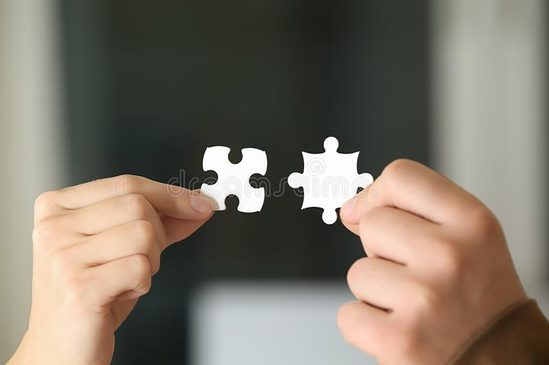 Male and female hands with pieces of puzzle, closeup royalty free stock photos