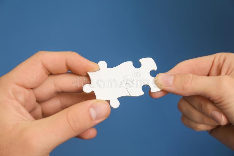 Male and female hands with pieces of puzzle on color background stock images
