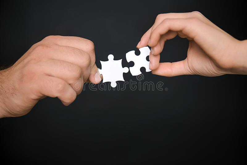 Male and female hands with pieces of puzzle on dark background stock photo