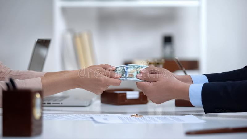 Male and female hands pulling money, dividing marital property during divorce royalty free stock photo