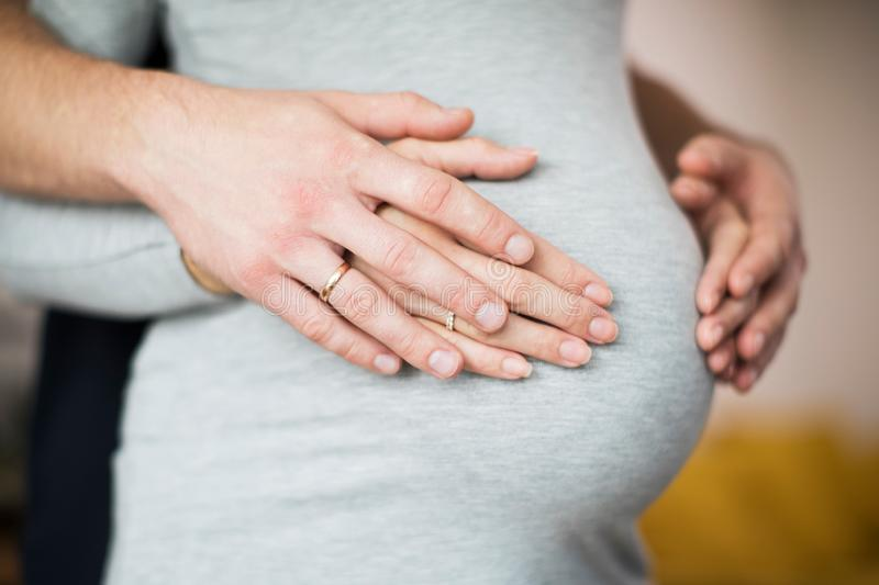 Close Up Of Male And Female Hands Resting On Pregnant Womans Stomach stock photos
