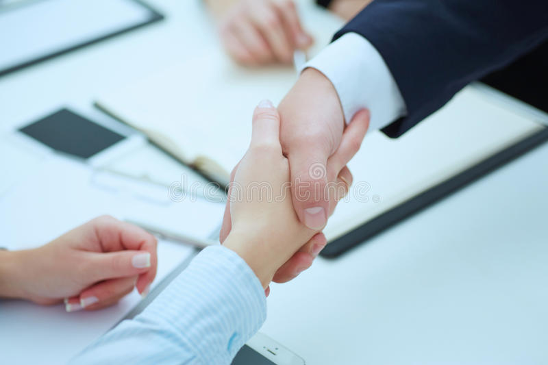 Male and female handshake in office. Businessman in suit shaking woman`s hand. stock image