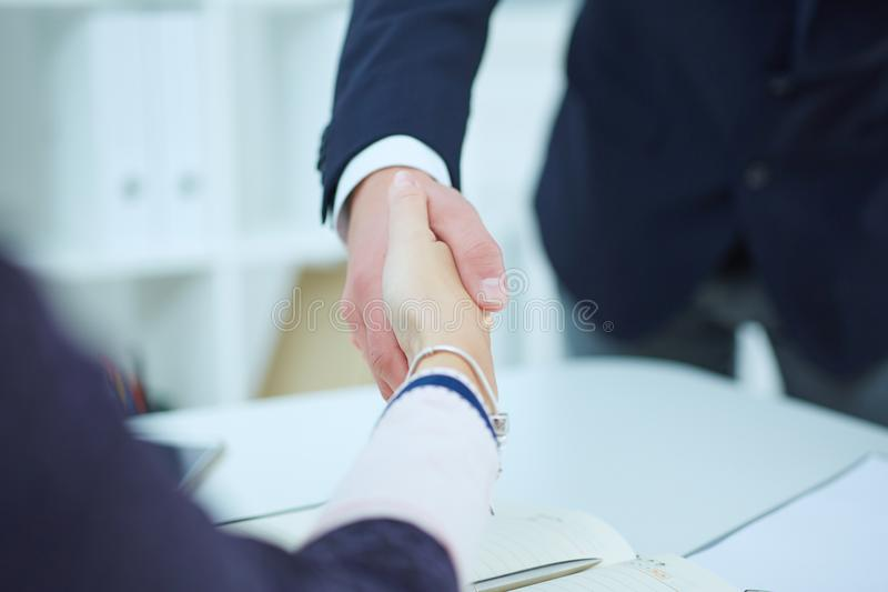 Male and female handshake in office. Serious business and partnership concept. stock image