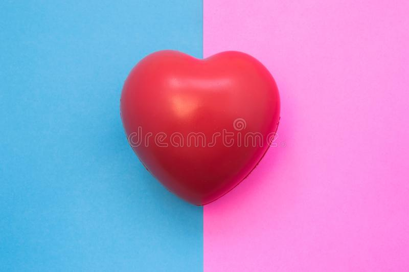 Male and female heart. Heart lies on two colors in background - blue and pink which symbolize man and woman. Medical features, uni. On, difference, feeling of royalty free stock image