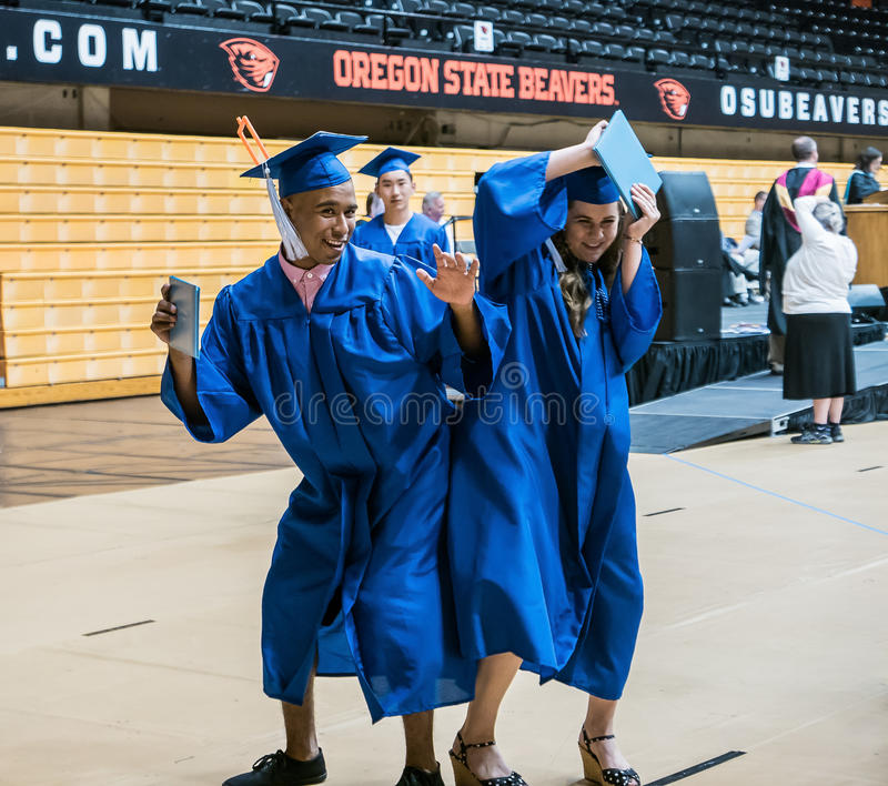 Male and female High school graduating seniors bump hips to celebrate diplomas royalty free stock images