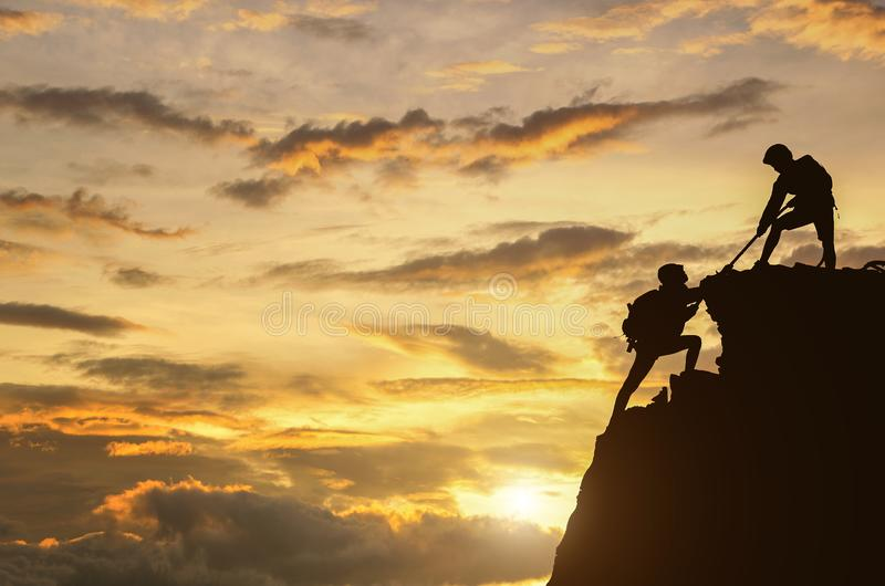 Male and female hikers climbing up mountain cliff and one of the. M giving helping hand. People helping and, team work concept stock photography