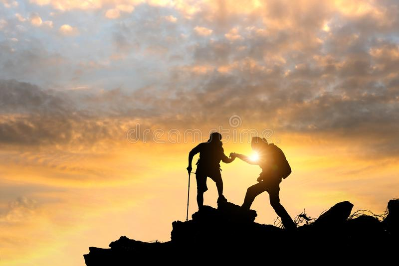 Male and female hikers climbing up mountain cliff and one of the. M giving helping hand. People helping and, team work concept royalty free stock photography