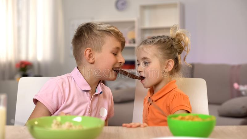Male and female kids eating chocolate together, brother sharing sweets sister stock photos