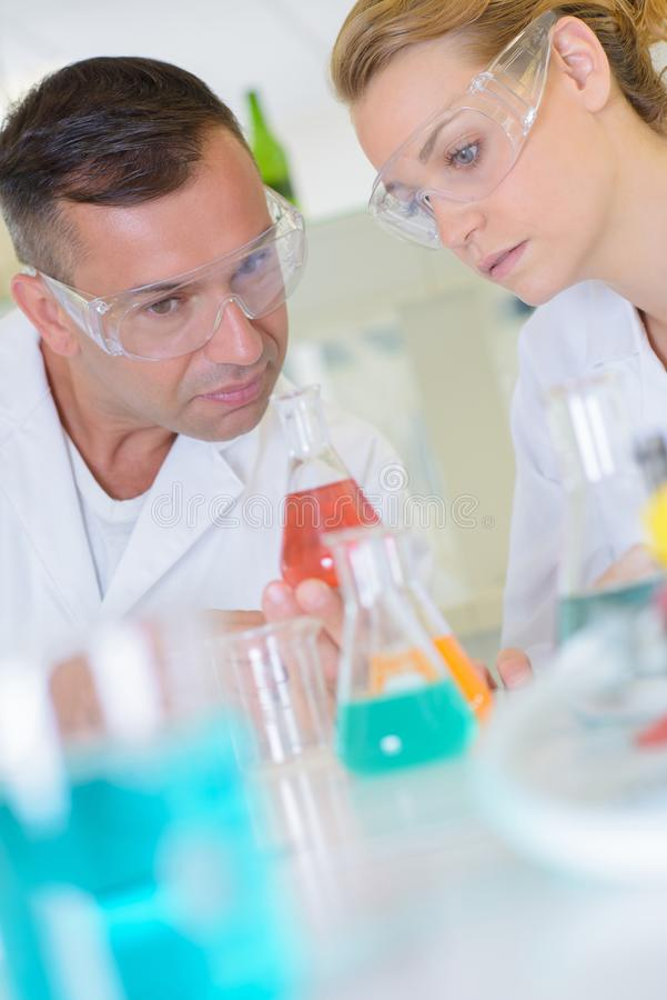 Male and female lab technicians looking at glass flasks. Man royalty free stock photos