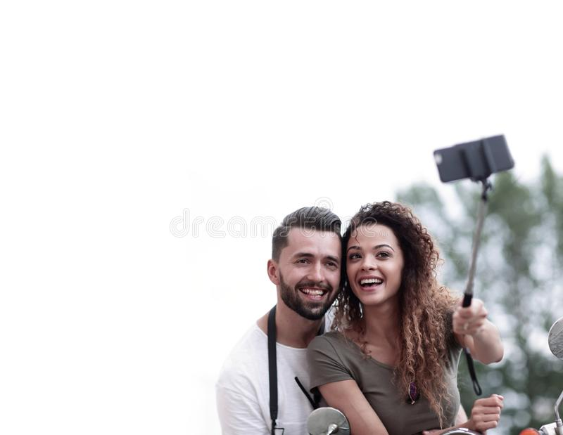 Male and female on motor scooters in a town. stock photo