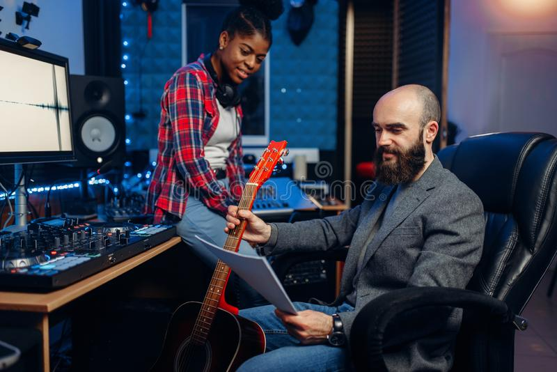 Male and female musicians, sound recording studio. Male and female musicians in sound recording studio. Performers on record, professional music processing stock photography