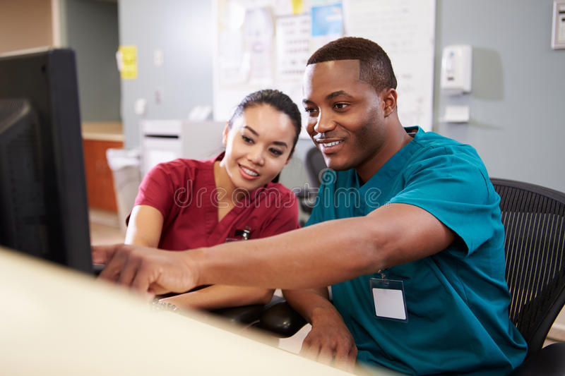 Male And Female Nurse Working At Nurses Station. Pointing To Computer Screen Smiling royalty free stock photo