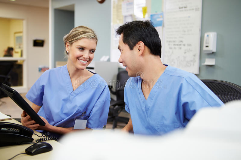 Male And Female Nurse Working At Nurses Station. Smiling At Each Other stock photo
