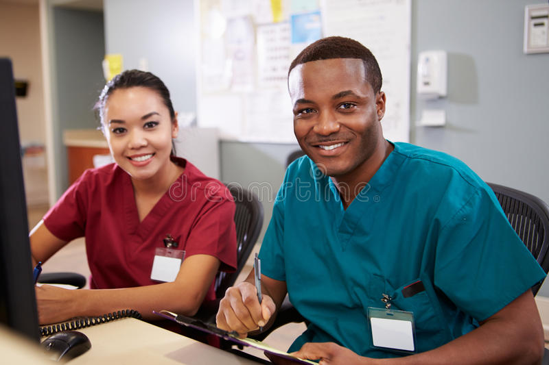 Male And Female Nurse Working At Nurses Station stock photography