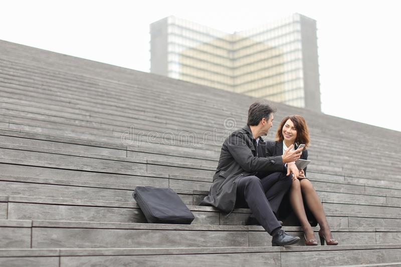 male and female office workers spend break sitting on stair royalty free stock images