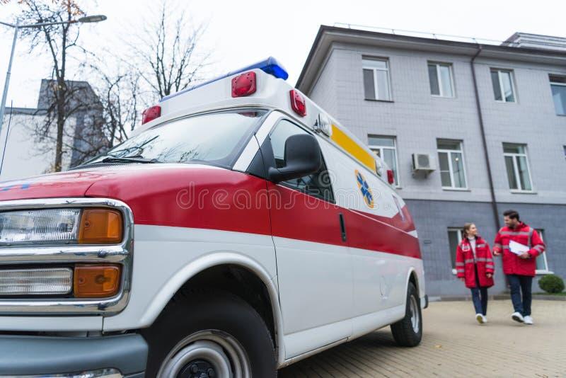 Male and female paramedics going. To ambulance royalty free stock image