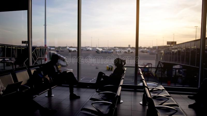 Male and female passengers sitting departure lounge, waiting for plane, travel royalty free stock images