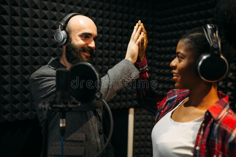 Male and female performers in recording studio. Male and female performers in headphones songs in audio recording studio. Musicians on record, professional music stock photography
