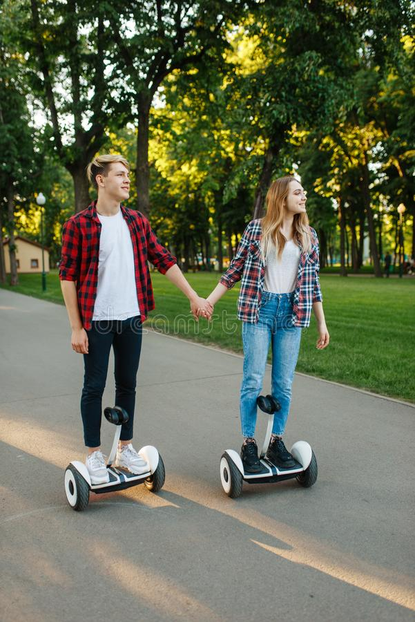 Male and female person riding on gyroboard in park stock images