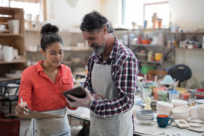 Male and female potter discussing over tablet pc. In the pottery workshop stock image