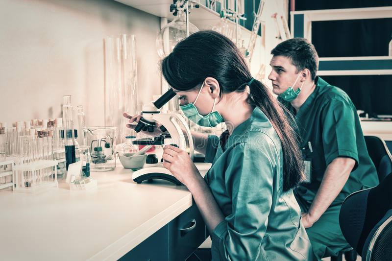 Male and female scientists in uniform is looking through a micro royalty free stock photo