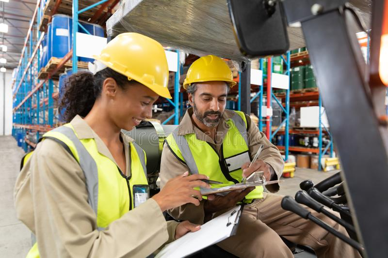 Male and female staff discussing over clipboard in warehouse. Multi-ethnic male and female staff discussing over clipboard in warehouse. This is a freight stock image