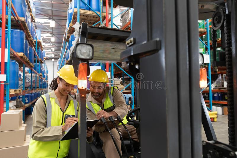 Male and female staff discussing over clipboard in warehouse. Multi-ethnic male and female staff discussing over clipboard in warehouse. This is a freight royalty free stock photos
