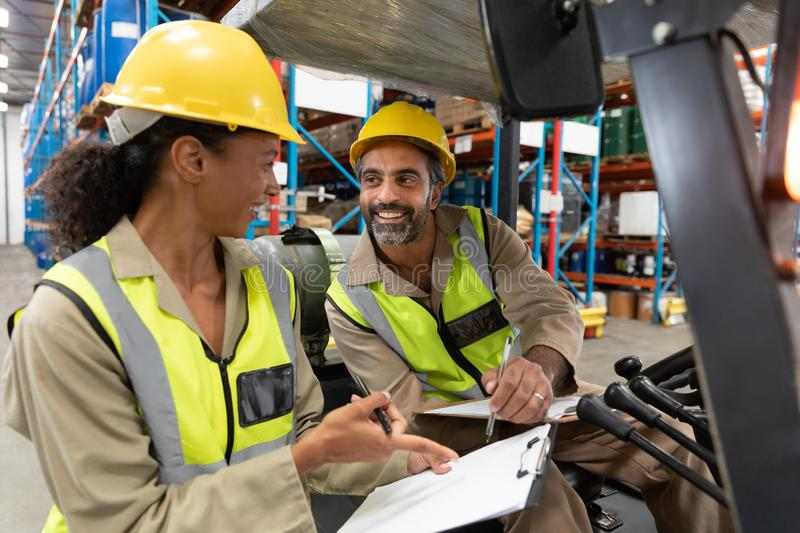 Male and female staff discussing over clipboard in warehouse. Multi-ethnic male and female staff discussing over clipboard in warehouse. This is a freight royalty free stock images