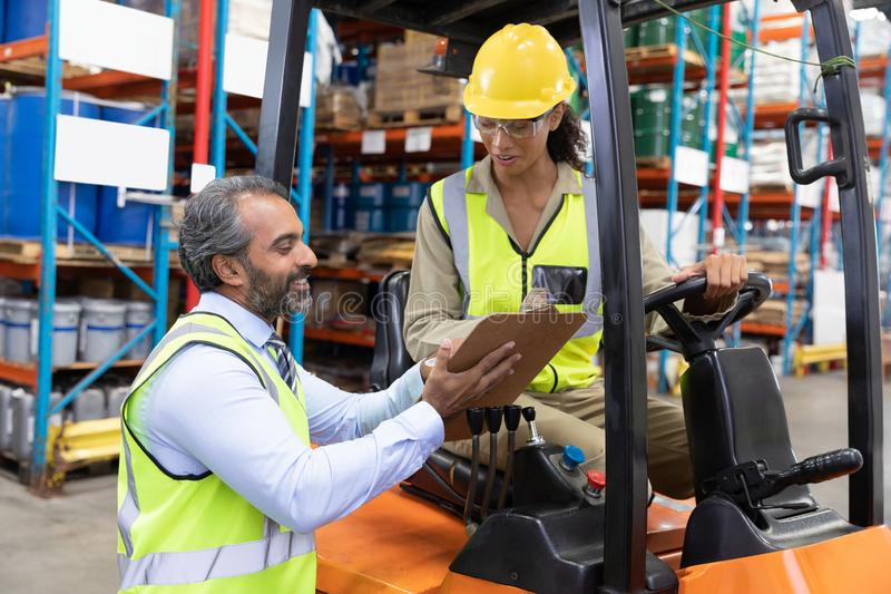Male and female staff discussing over clipboard in warehouse royalty free stock images
