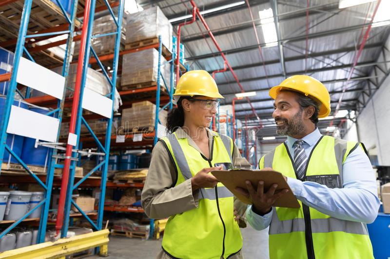 Male and female staff discussing over clipboard in warehouse royalty free stock image