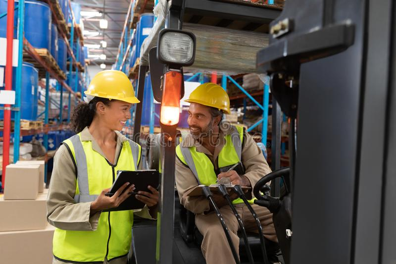 Male and female staff discussing over clipboard in warehouse. Multi-ethnic male and female staff discussing over clipboard in warehouse. This is a freight royalty free stock photo