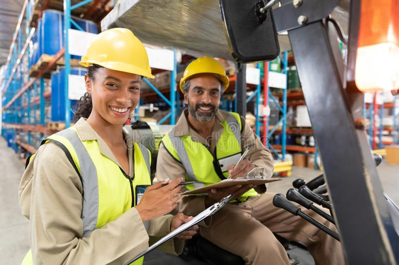 Male and female staff discussing over clipboard in warehouse. Portrait of Multi-ethnic male and female staff discussing over clipboard in warehouse. This is a royalty free stock photos