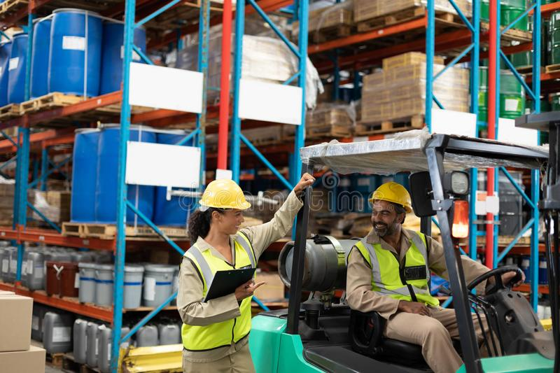 Male and female staff interacting with each other in warehouse. Happy male and female staff interacting with each other in warehouse. This is a freight stock image