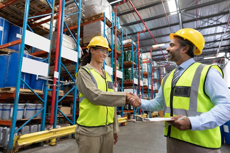 Male and female staff shaking hands with each other in warehouse stock photography
