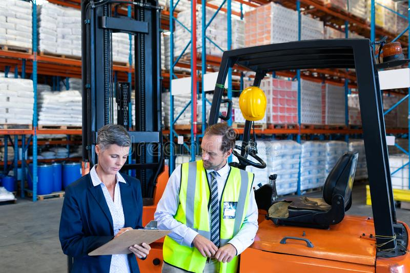 Male and female staff working together near forklift in warehouse royalty free stock images