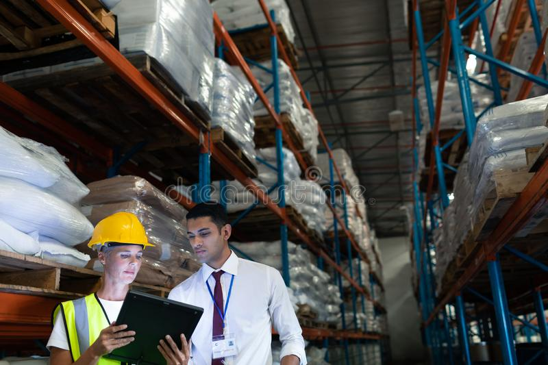 Male and female staffs discussing over digital tablet in warehouse. Front view of mixed-race Attentive male and female staffs discussing over digital tablet in royalty free stock photo