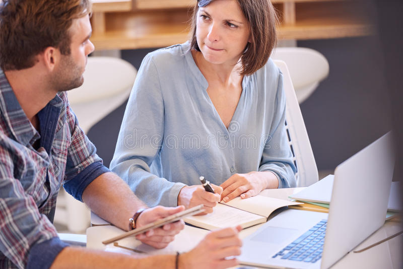 Male and female students brainstorming together for a colledge project. Adult caucasian male and female performing a brainstorming session together as the women royalty free stock images