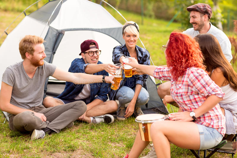 Male and female tapping with beer in front of tent. In forest stock photo