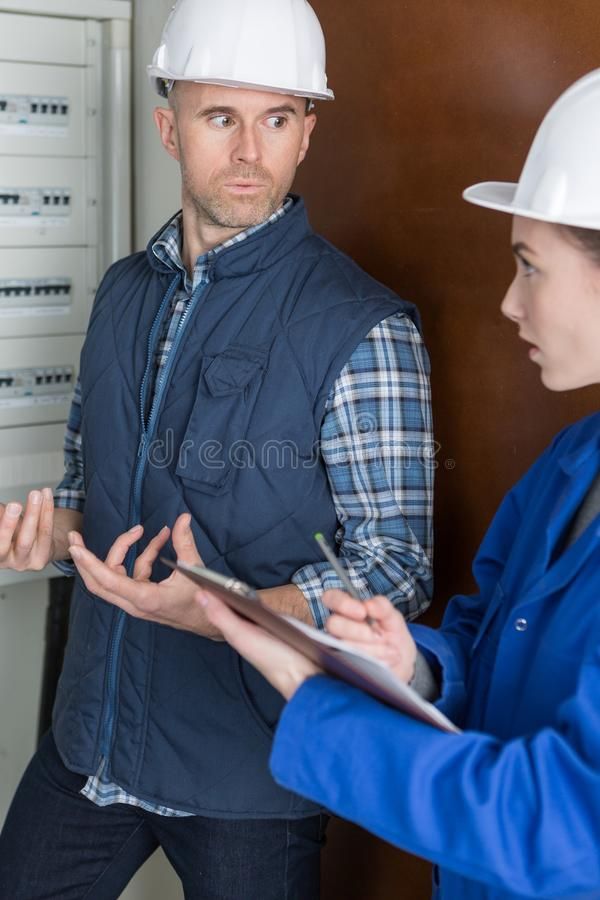 Male and female technicians in discussion by electric fusebox stock images
