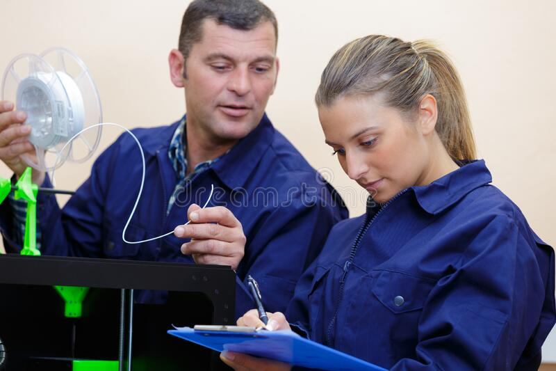 Male and female technicians working with 3d printer royalty free stock photos