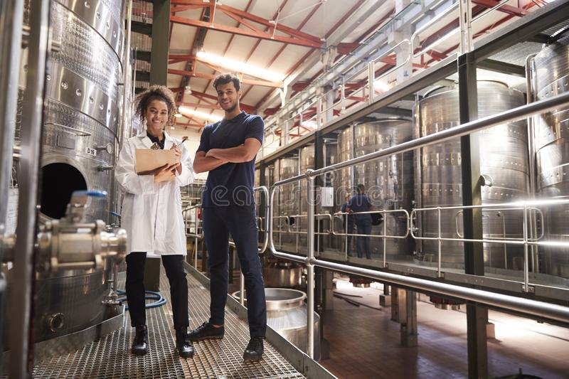 Male and female wine factory technicians smiling to camera stock photo