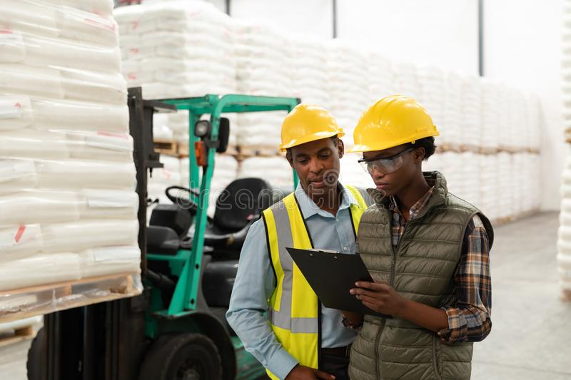 Male and female worker discussing over clipboard in warehouse. Front view of male and female worker discussing over clipboard in warehouse. This is a freight royalty free stock image