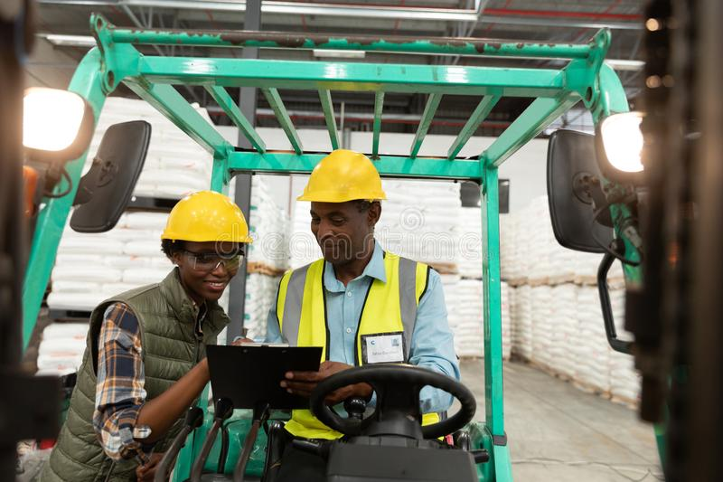 Male and female worker discussing over clipboard in warehouse. Front view of male and female worker discussing over clipboard in warehouse. This is a freight stock photo
