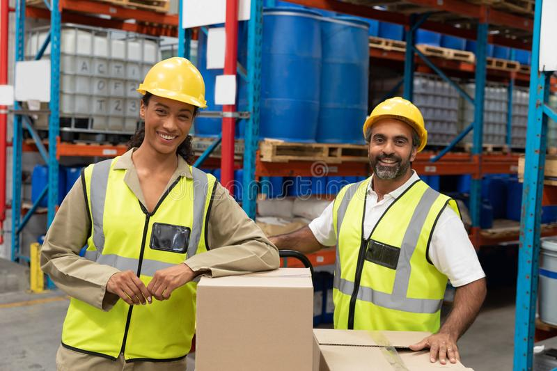 Male and female worker looking at camera in warehouse. Happy male and female worker looking at camera in warehouse. This is a freight transportation and stock images